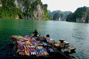 Händler wollen den Touristen auf den Cruise-Ships in der Halong BAy etwas verkaufen. Boat-traders in Halong Bay trying to sell their goods to the tourists on the cruise-ships