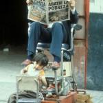 A child is cleaning the shoes of a mexican businessmen, which is reading in the newspaper all about the poverty in MexicoEin mexikanische Geschäftsmann lässt sich von einen Kind die Schuhe putzen und liest in der Zeitung über die Armut in Mexico.