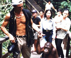 Spaziergang mit einem Orang Utan in Borneo: Der Zürcher Fotojournalist Gerd Müller nimmt einen Orang Utan an der Hand, der ihm den Weg versperrte und sich an sein Bein klammerte und spaziert mit ihm zur Rehabilitationsstation in Sarawak. The Swiss Photojournalist is walking hand in hand wit a handicaped Orang Utan in Sarawak, Borneo.