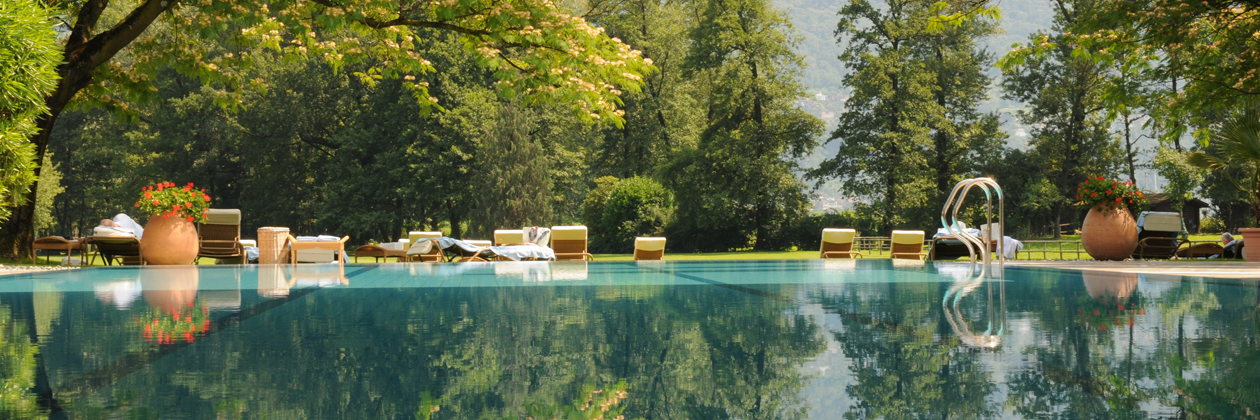 Der Pool des  Luxushotel Castello del Sole in Ascona mit Blickauf die 110 ha grosse Parkanlage. The view from the pool to the giant hotel park of Castello del Sole
