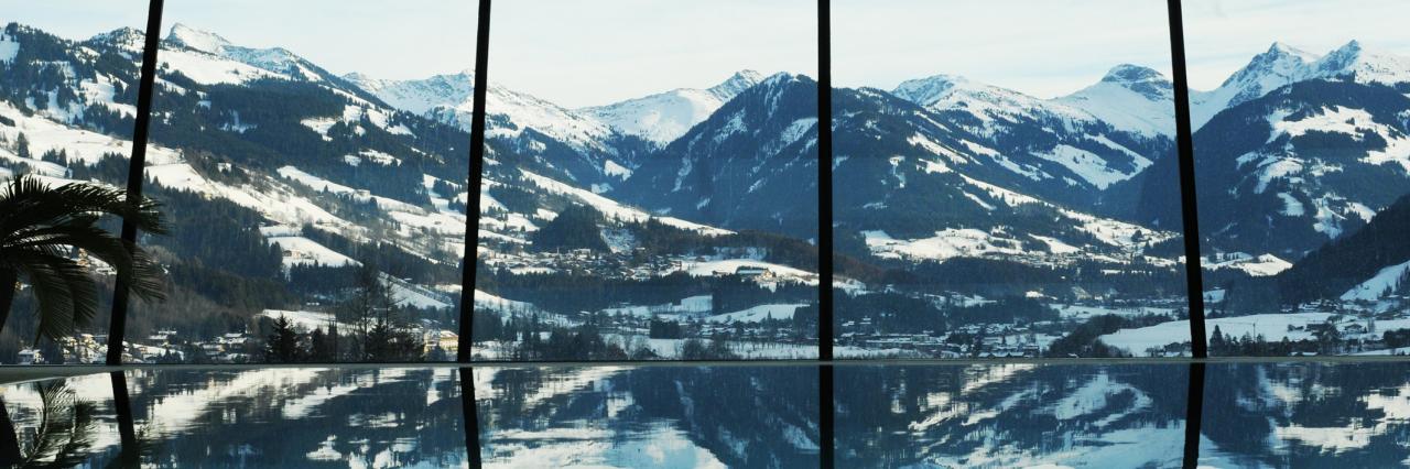Die Aussicht vom Schlosshotel Lebenberg Indoor Pool auf der obersten Etages des Kitzbühler Viersterne-Seminarhotels