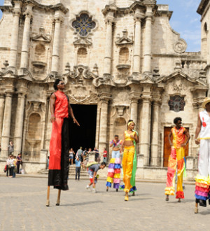 Kuba: Stelzen-Tänzerinnen bewegen sich anmutig auf dem Kopfsteinpflasterplatz im Zentrum Havannas. Dance-Show in Havanna-City.