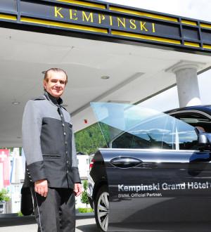 Der Kempinski voiturier bringt seine Gäste zum Bahnhof St. Moritz oder zum Flugplatz in Samedan. The Kempinski des Baigns chauffeur takes the guests to the train station in St. Moritz or to the airport in Samedan.